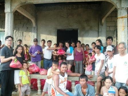 Joward Blaza, far left in grey, helped in the distribution of some relief goods to Adventist members in Sua church in the town of San Dionisio, northern Ilo-ilo. San Dionisio remains to be one of the lesser reached towns with people needing relief assistance after typhoon Haiyan ruined their houses and livelihood. [photo contributed by Joward Blaza]
