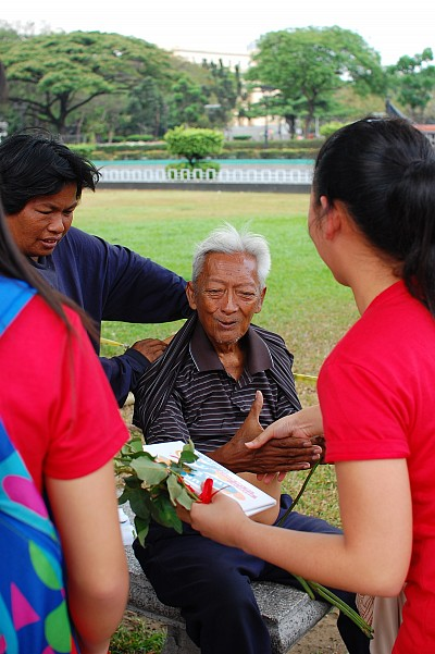 82-year-old Mang Noel reacts upon receiving a flower and encouragement cards from a group of Adventist youth celebrating Global Youth Day through acts of compassion in a Manila park, March 15. [photo by RJ Almocera]