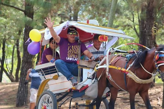 Mt. Klabat University (UNKLAB) president, Dr. Tommy Mambu, waves from a small horse-drawn cart, at the opening parade on October 15 during the university's 50th anniversary celebration. The event lasted for three days. [photo contributed by J. Rondonuwu]